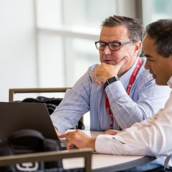 Two conference goers looking up something on a laptop